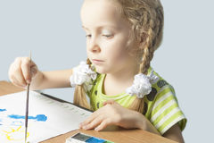 Concentrated little caucasian blond girl drawing Royalty Free Stock Image