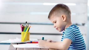 Concentrated little creator boy drawing beautiful colorful art picture using marker at album