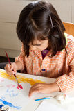 Concentrated little girl painting Royalty Free Stock Image