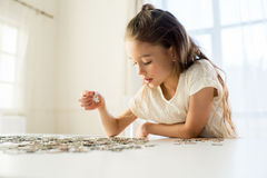 Concentrated little girl playing with puzzles at home Royalty Free Stock Photography