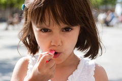 Little girl putting on lipstick Royalty Free Stock Photos
