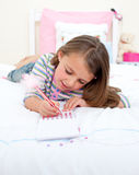 Concentrated Little girl writing on a notebook Royalty Free Stock Image