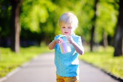 Concentrated little kid boy drawing with colored chalk on asphalt Stock Photos