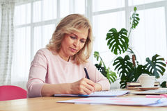 Concentrated madam drinking coffee while writing Royalty Free Stock Images