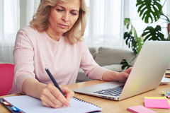Concentrated madam writing while working in laptop Stock Photo