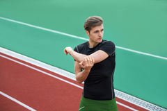 Concentrated male athlete make stretching exercises. Image of young concentrated male athlete make stretching exercises outdoors. Looking aside Stock Photo