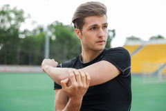 Concentrated male athlete make stretching exercises outdoors. Picture of young concentrated male athlete make stretching exercises outdoors. Looking aside Stock Images