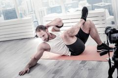 Concentrated male blogger training belly muscles. Abs in tone. Focused pensive male blogger lifting leg and shoulders while touching floor and training near Royalty Free Stock Photo