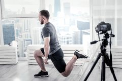 Concentrated male blogger training legs muscles. Another circuit. Ambitious professional male blogger doing exercise while using training for it and posing in Royalty Free Stock Images
