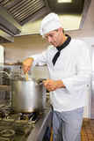 Concentrated male chef preparing food in kitchen. Side view of a concentrated male chef preparing food in the kitchen royalty free stock image