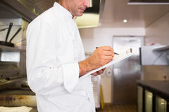 Concentrated male cook writing on clipboard in kitchen Royalty Free Stock Photos