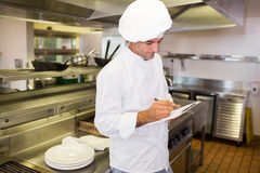 Concentrated male cook writing on clipboard in kitchen Stock Photography
