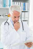 Concentrated male doctor looking at reports Royalty Free Stock Photography