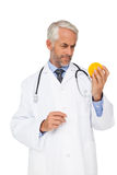 Concentrated male doctor looking at stress ball Stock Photography