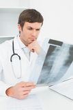 Concentrated male doctor looking at xray picture of spine Stock Photo