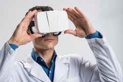 Concentrated male doctor  studying virtual reality. Virtual experience. Ambitious pleasant male doctor touching VR glasses while posing on the  background and Royalty Free Stock Image