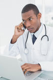 Concentrated male doctor using cellphone and laptop Stock Photography
