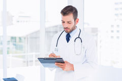 Concentrated male doctor writing reports in clipboard Stock Photo