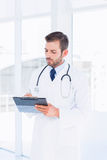 Concentrated male doctor writing reports in clipboard Royalty Free Stock Photos