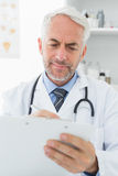 Concentrated male doctor writing reports Stock Photo
