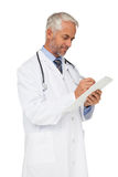 Concentrated male doctor writing reports Royalty Free Stock Photo