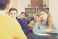 Concentrated male and female students following explanations of. Teacher in class Royalty Free Stock Photos