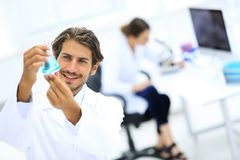Scientific researcher working in laboratory. Concentrated male laboratory scientist holding flask with blue liquid showing it to student at science lab Royalty Free Stock Photography