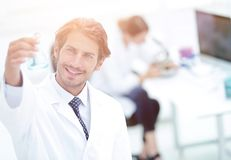 Scientific researcher working in laboratory. Concentrated male laboratory scientist holding flask with blue liquid showing it to student at science lab Royalty Free Stock Images