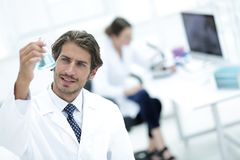 Scientific researcher working in laboratory. Concentrated male laboratory scientist holding flask with blue liquid showing it to student at science lab Stock Image