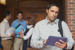 Concentrated male mature student holding his tablet standing in the corridor. With his classmates Stock Images