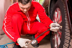 Concentrated male motor mechanic checking the air pressure of a. Tyre crouching down alongside the vehicle with the gauge from the pump in his gloved hand Royalty Free Stock Photo