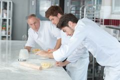 Concentrated male pastry with apprentices royalty free stock image