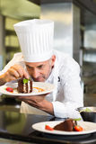 Concentrated male pastry chef decorating dessert in kitchen Royalty Free Stock Photography
