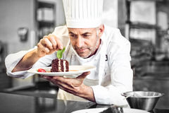 Concentrated male pastry chef decorating dessert in kitchen Stock Photo