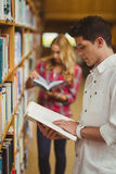 Concentrated male student reading book Royalty Free Stock Images