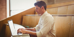 Concentrated male student using laptop. In lecture hall Stock Images