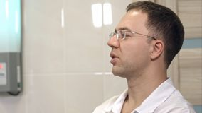 Concentrated male surgeon in glasses controlling surgery. Close up shot. Professional shot in 4K resolution. 097. You can use it e.g. in your commercial video Royalty Free Stock Photos