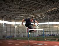 Concentrated male track and field athlete jumping over the hurdle.Indoor training. The shot of concentrated male track and field athlete jumping over the hurdle royalty free stock images