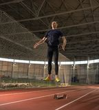 Concentrated male track and field athlete warming up before hurdling training. The shot of concentrated male track and field athlete warming up before hurdling royalty free stock photo