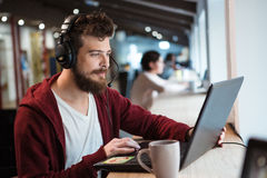 Concentrated male using headset and laptop. Concentrated handsome male with beard using headset and laptop Stock Photography