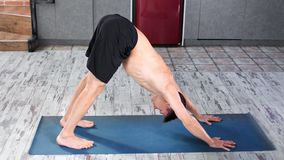 Concentrated male yogi master doing exercise downward dog on mat high angle. Fitness man having slim strong body enjoying practicing yoga stretching workout stock video