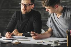 Concentrated males doing paperwork. Portrait of concentrated young males doing paperwork in modern office. Teamwork concept Stock Photography