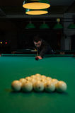Concentrated man aiming the billiard ball. Snooker game background. Shallow depth of field royalty free stock photography