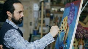 Concentrated man artist painting still life picture on canvas in art studio indoors. Concentrated young man artist painting still life picture on canvas in art stock video footage