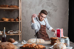 Concentrated man baker standing at bakery near bread. Image of young concentrated man baker standing at bakery near bread. Looking aside royalty free stock images