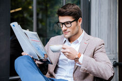 Concentrated man with coffee and magazine sitting in outdoor cafe. Concentrated young man in glasses with coffee and magazine sitting in outdoor cafe royalty free stock image