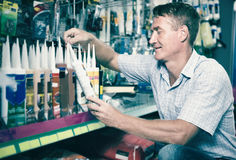 Concentrated man customer choosing sealant tube in hypermarket Royalty Free Stock Photos