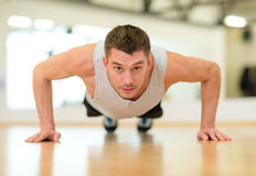 Concentrated man doing push-ups in the gym Stock Photography