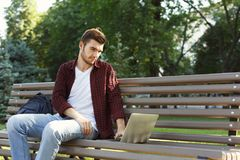Concentrated man working on his laptop outdoors. Concentrated man in glasses working on his laptop in pleasant atmosphere outdoors, in park. Technology Royalty Free Stock Photo