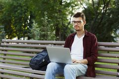 Concentrated man working on his laptop outdoors. Concentrated man in glasses working on his laptop, sitting on bench in park. Technology, communication Royalty Free Stock Image